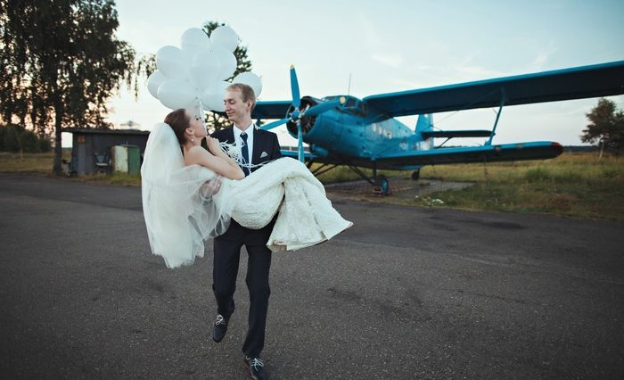 Lovely wedding couple near old blue plane